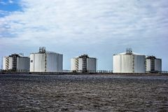 Industria oil storage tanks on the water front royalty free stock image