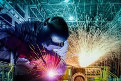 Industrial worker welding procecc by arc with sparks light in factory. Industrial worker welding procecc by arc with sparks light in. Craftsman erecting technical steel industrial steel welding by MIG Weld in factory, Wear equipment protective the leather gloves and mask, on grinding light and structure factory background, repair, arc, protection, metal, manufacturing, skill, worker, workplace, welder, smoke, spark, safety, hot, fire, laboring, industry, construction, job, laborer, making, improvisation, fabricate, fix, flash, joint, proletariat, welded, workman, trained, proletarian, build, flaming, flame, heavy, rod, metalwork, tool, assembly, close, up, working, duty, manual stock photography