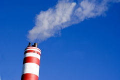 Industrial. Water steaming chimney blowing clouds into the blue sky Stock Photography