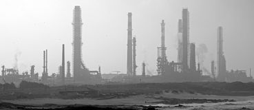 Industrial. Black an white panorama of a refinery in a preventive maintenance (early morning light). Coexistence between this old refinery and population seems Stock Image