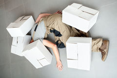 Industrial accident. Worker crushed by several heavy cartons during work Royalty Free Stock Photos