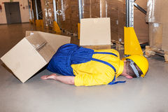 Industrial accident. Worker in hard hat hit by cardboard in warehouse Royalty Free Stock Images