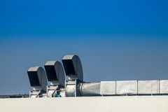 Industrial air conditioning and ventilation systems on a roof. On blue isolated Stock Photo