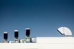 Industrial air conditioning and ventilation systems on a roof. On blue isolated Stock Images