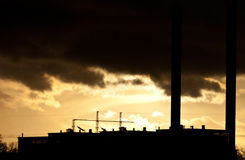 Industrial air pollution. Industrial plant spewing out fumes from three chimneys Royalty Free Stock Photo