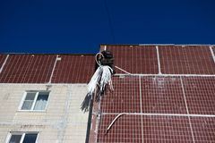 Industrial alpinism. worker closes the gap between the panels of the house outside. Maintenance of an apartment building. Overhaul. reportage royalty free stock image