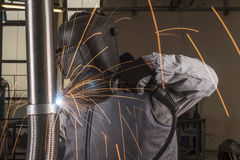 Industrial arc welder working in factory. Welder with protective equipment welding metal in factory Royalty Free Stock Photos