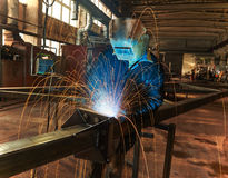 Industrial arc welding work. Industrial welder worker at the factory arc welding process with sparks Royalty Free Stock Photos