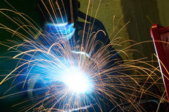 Industrial arc welding work. Industrial welder worker at the factory arc welding process with sparks Royalty Free Stock Images