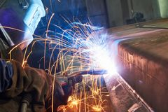Industrial arc welding work. Industrial welder worker at arc welding process with sparks. Focus on sparkle Stock Image