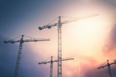 Industrial background with cranes over sunset sky Royalty Free Stock Photos