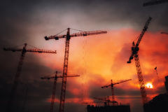 Industrial background with cranes over sunset sky Stock Photo