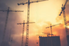 Industrial background with cranes over sunset sky Stock Image