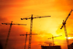 Industrial background with cranes over sunset sky Stock Photos