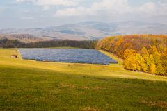 Solar panels on green meadow. Industrial background on renewable resources with solar power plant in pasture surrounded by forest. Sunny autumn day Stock Photography