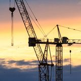 Industrial background with silhouette of construction crane at sunset