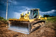 Industrial backhoe, bulldozer moving earh and sand in sandpit Stock Photos