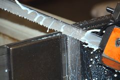 Industrial bandsaw cutting metal. Action shot of an industrial bandsaw cutting through metal, showing shavings and coolant frozen in time Royalty Free Stock Images