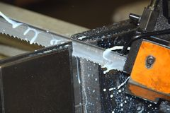 Industrial bandsaw cutting metal. Action shot of an industrial bandsaw cutting through metal, showing shavings and coolant frozen in time Stock Photography
