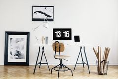 Industrial basket with kraft paper rolls and a framed poster in a white, minimalist home office interior of a freelancer architect. Real photo. concept royalty free stock photography