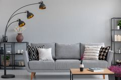 Industrial lamp above stylish grey couch , real photo with copy space. Industrial black metal lamp above stylish grey couch with patterned pillows, real photo stock photography