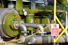 Industrial Boilers and Pipework. Green Industrial Boilers and Pipework with Warning Sign stock photography