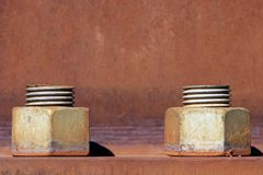 Industrial Bolts - Teamwork. A pair of large industrial bolts on a rusted metal surface stock image
