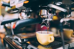 Professional brewing - coffee bar details. Espresso coffee pouring from espresso machine. Barista details in cafe shop Royalty Free Stock Photos