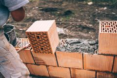 Industrial bricklayer installing bricks on construction site Royalty Free Stock Image