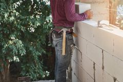 Industrial bricklayer installing bricks on construction site Stock Images