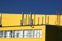 Industrial building. Yellow industrial building on sky background Stock Photography
