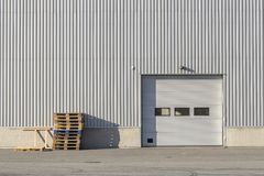 Industrial Building with Garage Door. And Box Pallets royalty free stock photos