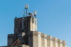 Industrial building with GSM antennas on roof. Isolated on blue sky Royalty Free Stock Photos