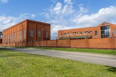 Industrial building with office building. Production room made of brick. Red brick fence. Small factory. royalty free stock images