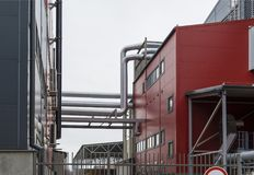 Industrial building painted in red and gray tones with a chimney. Gray sky. Of the pipes coming out of the smoke Stock Images