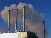 Industrial building. Pipe against the sky belching smoke. Pipe against the sky belching smoke. Industrial building Royalty Free Stock Photo