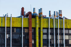 Industrial building with pipes. Industrial yellow  building with orange and  steel pipes Royalty Free Stock Image