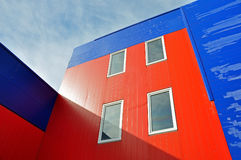 Industrial building of red and blue sandwich panels. Grodno, Belarus - September 7, 2016: Industrial building of red and blue sandwich panels with windows lit Royalty Free Stock Photography