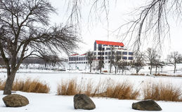 Industrial building viewed from across a frozen pond Royalty Free Stock Images