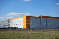 Industrial building, warehouse. Blue sky with clouds stock images