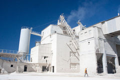 Industrial building and worker. Industrial worker, white factory and blue sky Stock Image