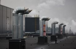 Industrial buildings and pipes on the roof of the plant. Steam coming from the workshop stock photo