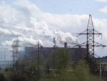 Industrial buildings with smoking chimneys and  high-voltage overhead power line Stock Photo
