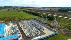Industrial buildings and switchgears at substation. Panoramic view blue industrial buildings and switchgears at substation against green plants near road stock footage