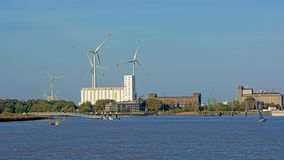 Industrial buildings and wind turbines along a dock in the port of Antwerp. Flanders, Belgium royalty free stock photos