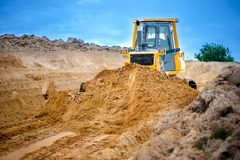 Industrial bulldozer and excavator working with earth in sandpit Stock Image