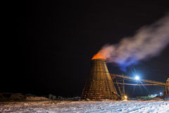 Industrial burner. A large coned industrial wood chip burner with a fire inside shooting sparks out to the top in a sawmill yardsite at night in winter stock images