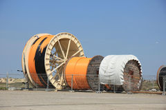 Industrial cables. Industrial underground cables on large wooden reels, different sizes Royalty Free Stock Images