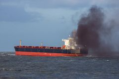 Air pollution industrial ship. Industrial cargo ship causing air pollution leaving the Port of Rotterdam royalty free stock photos