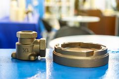 Industrial casting parts vane pump or propeller blades and water joint Brass fittings on blue table.  royalty free stock images